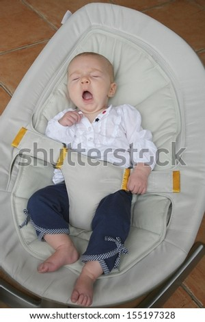 Sweet newborn baby girl sleeps peacefully and yawns relaxing in bouncer chair - stock photo