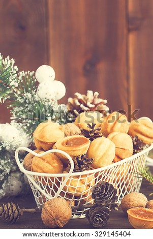 Sweet nuts and cones in a metal basket with white Christmas decoration, toned, selective focus - stock photo