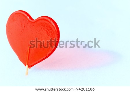 Sweet One  Valentines heart made of sugar with   reflection effect on snow - stock photo