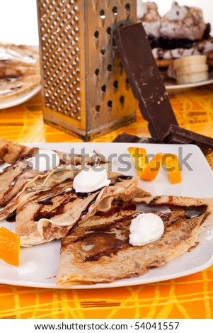 sweet  pancakes decorated with orange peel and whipped cream - stock photo