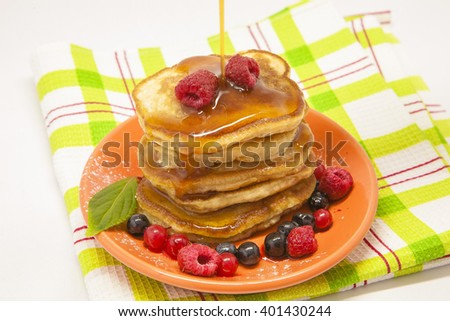 Sweet pancakes with honey, raspberry and blueberry on plate, morning photo
