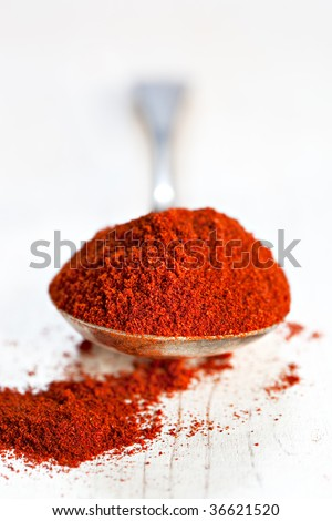 Sweet paprika, on an old silver spoon on rustic timber.  Very shallow dof.