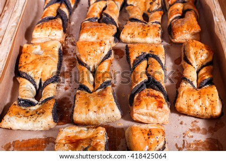 Sweet pastry, Puff pastry with poppy filling on shelf in Bakery shop. Pastries and bread in a bakery - stock photo