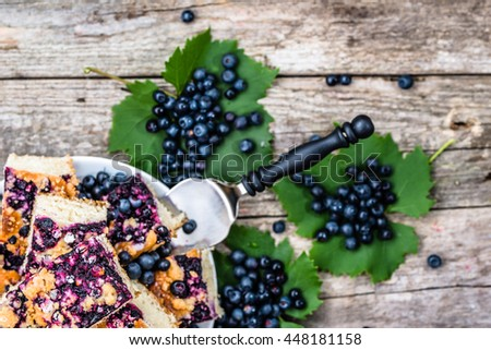Sweet pastry with blueberry fruits on yeast pie, summer baking concept from above - stock photo