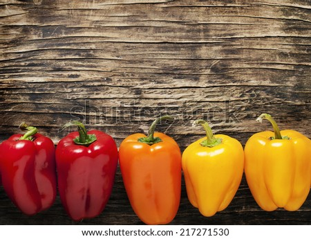 Sweet peppers on wooden background - stock photo