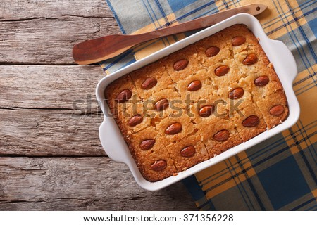 Sweet pie Basbousa (Namoora) with almond in baking dish on the table. horizontal top view