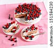 Sweet pie with whipped cream, raspberries and chocolate and blueberries served on a pink tablecloth - stock photo