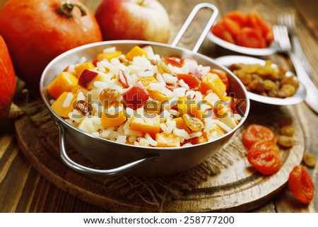 Sweet pilaf with pumpkin, apples and dried fruit on the table