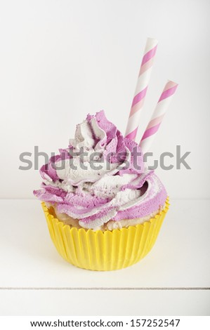 Sweet pink cupcake with straws on a white wooden background