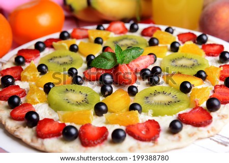 Sweet pizza with fruits on table close-up - stock photo