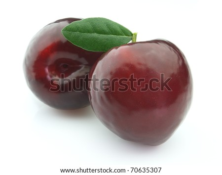 Sweet plums with leaves - stock photo