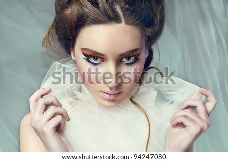sweet portrait of an attractive young brunette girl with white material around her neck sophisticated makeup looking at the camera against grey background - stock photo