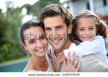 Sweet portrait of couple with little girl - stock photo