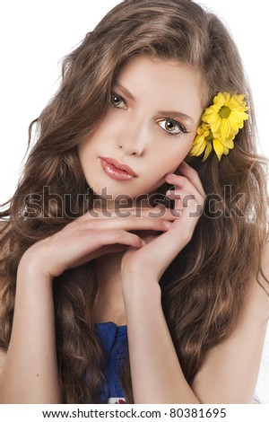 sweet portrait of fresh and youn brunette with flower in hair looking in camera