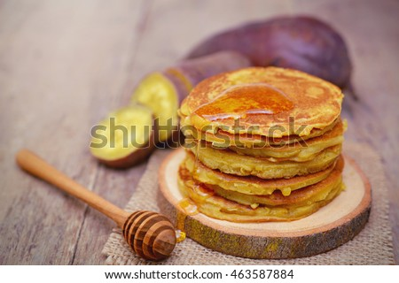 Sweet potato pancakes with honey on wooden plate.