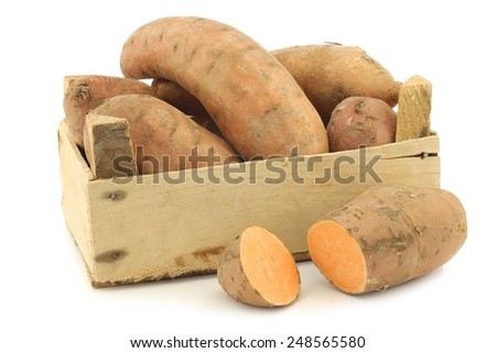 sweet potatoes and a cut one in a wooden crate on a white background - stock photo