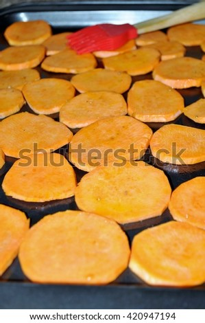 Sweet potatoes chips on a tray prepared to bake. Seasoning used : olive oil, salt, pepper, paprika, rosemary, garlic fresh, garlic powder.  - stock photo