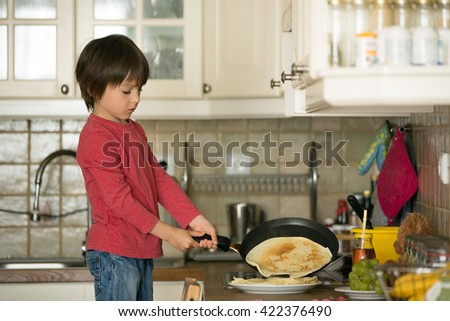 Sweet preschool child, helping his mom in the kitchen, making pancakes in the morning, happy childhood - stock photo