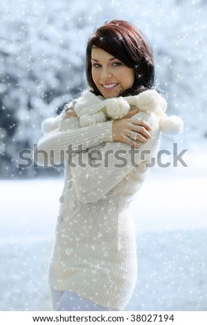 sweet pretty girl in white in a winter park with stur dust all around - stock photo