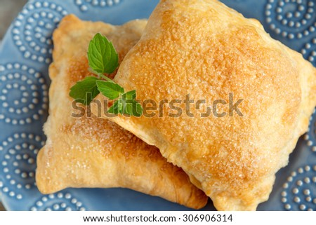 Sweet puff pastry with sugar and mint close up on blue plate - stock photo