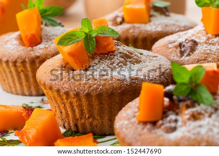 sweet pumpkin muffins with walnuts and powdered sugar - stock photo