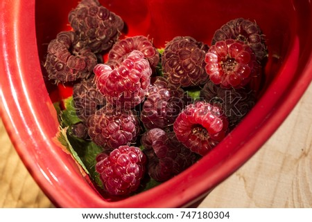 Sweet raspberries in bowl on wooden table. Close up, top view, high resolution product