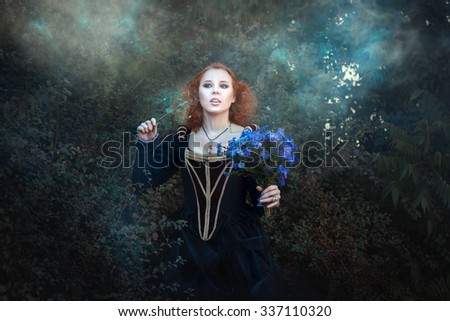 Sweet red-haired fairy in the woods.  In her hand she had a magic wand. - stock photo