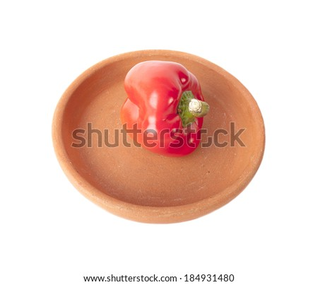 Sweet red pepper in clay bowl isolated on a white background.
