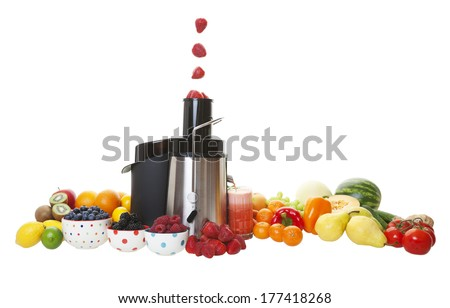 Sweet, ripe strawberries fall into the juicing machine hopper, and the extracted juice flows into the glass.  Shot on white background. - stock photo
