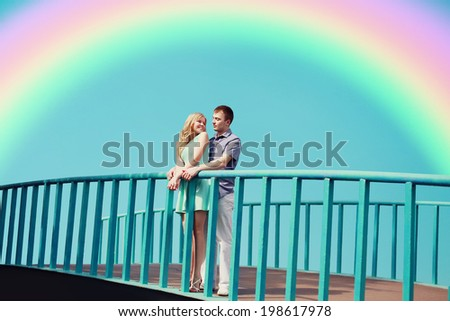 Sweet romantic happy carefree couple having fun outdoors in the city park, blue sky, rainbow. Valentine's day, summer holidays, love, relationships - concept - stock photo