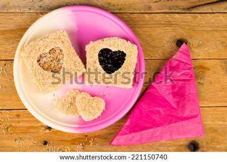 Sweet sandwich with a heart shape cut out of the bread - stock photo