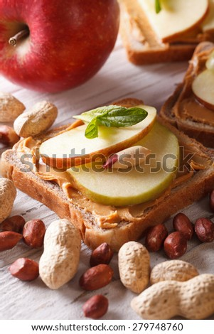 Sweet sandwich with peanut butter and apple close up. vertical  - stock photo