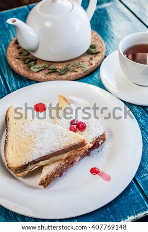 sweet sandwich with peanut oil on a white plate with cap of tea - stock photo