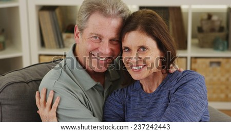 Sweet senior couple cuddling on couch