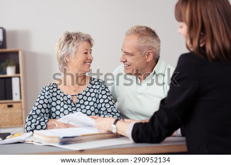 Sweet Senior Couple Smiling Each Other While Talking to a Female Agent Inside the Office. - stock photo