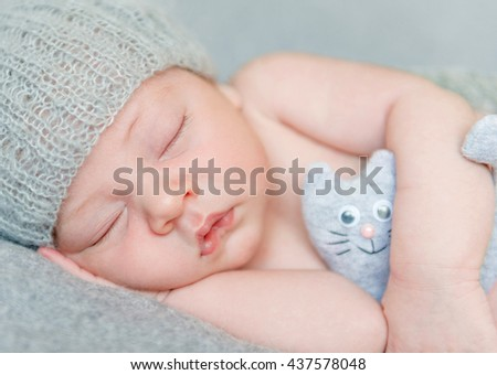 sweet sleeping newborn baby in gray hat with toy, close-up - stock photo