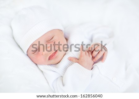 Sweet sleeping smiling newborn baby in a white hat - stock photo