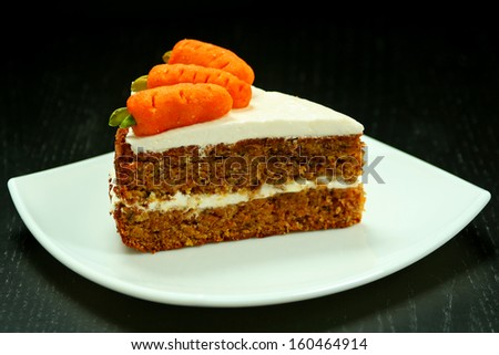 Sweet slice of carrot cake on white plate - stock photo