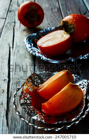 Sweet slice persimmon on rustic wooden background. Selective focus. - stock photo