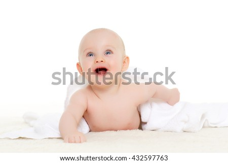 Sweet small baby covered with a towel, lies on a plaid on a white background.