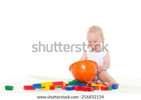 Sweet small baby with helmet and toy  building bricks  on a white background. Concept of construction. - stock photo