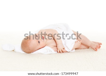 Sweet small baby with  towel lies on the plaid on a white background.