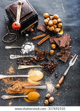 Sweet spices in the spoons and chocolate on a table black - stock photo
