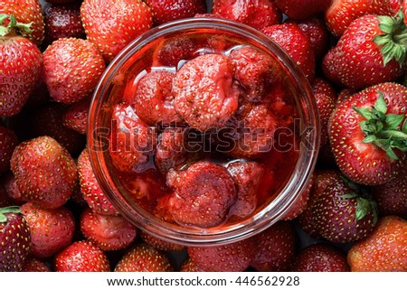 Sweet strawberry jam on fresh ripe berries. Top view. - stock photo