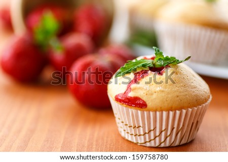 sweet strawberry muffins with strawberries on wooden table - stock photo