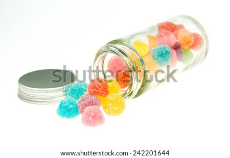 Sweet sugar candies in glass jars on white background  - stock photo
