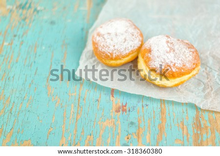 Sweet sugary donuts on rustic wooden kitchen table, tasty bakery doughnuts on crumpled baking paper in vintage retro toned image - stock photo