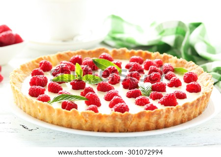 Sweet tart cake with raspberries on white wooden background - stock photo