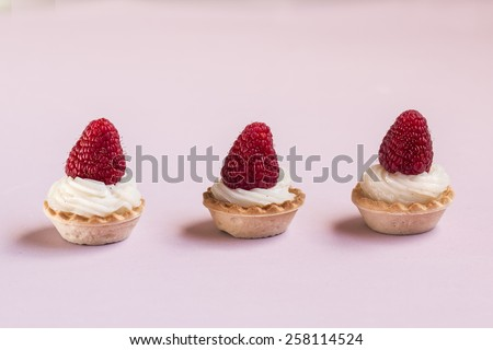 Sweet tartlets filled with cream and raspberry on pink background - stock photo