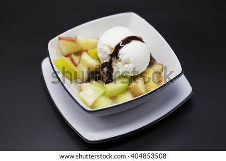 Sweet tasty fruit salad with a scoop of ice cream and milk chocolate. - stock photo